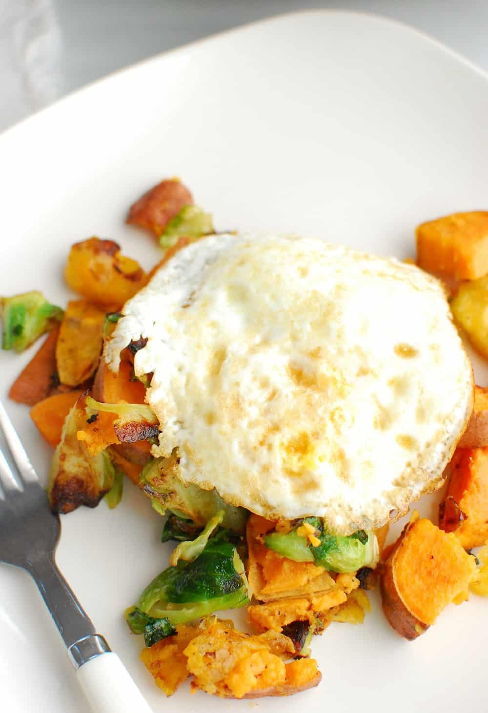 a plate with sweet potatoes, brussels sprouts, plantains, and an egg on top