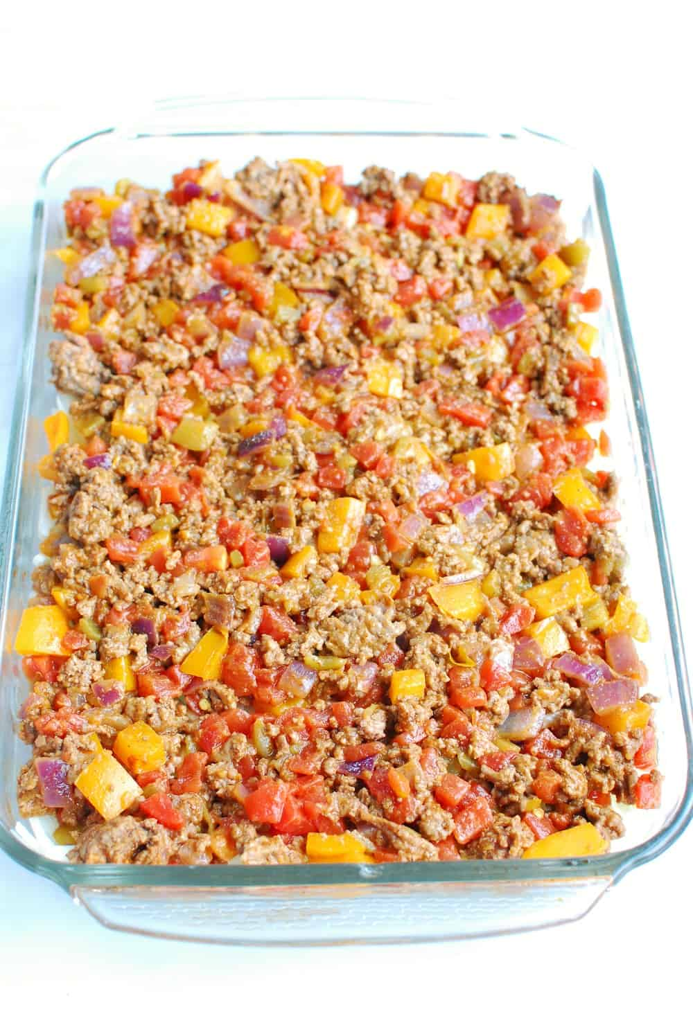 a casserole dish filled with hashbrown potatoes then topped with a ground beef mixture