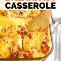 a taco breakfast casserole in a large dish with a wooden spoon scooping a piece out