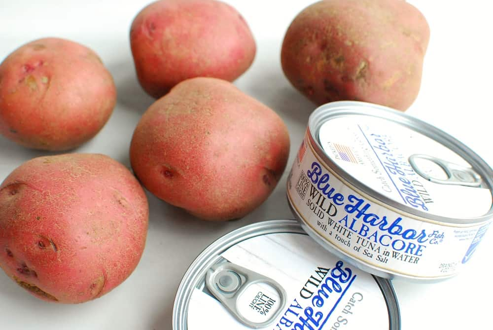 several cans of tuna next to some red potatoes