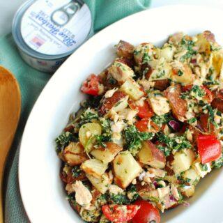 a bowl of tuna potato salad next to a can and blue napkin