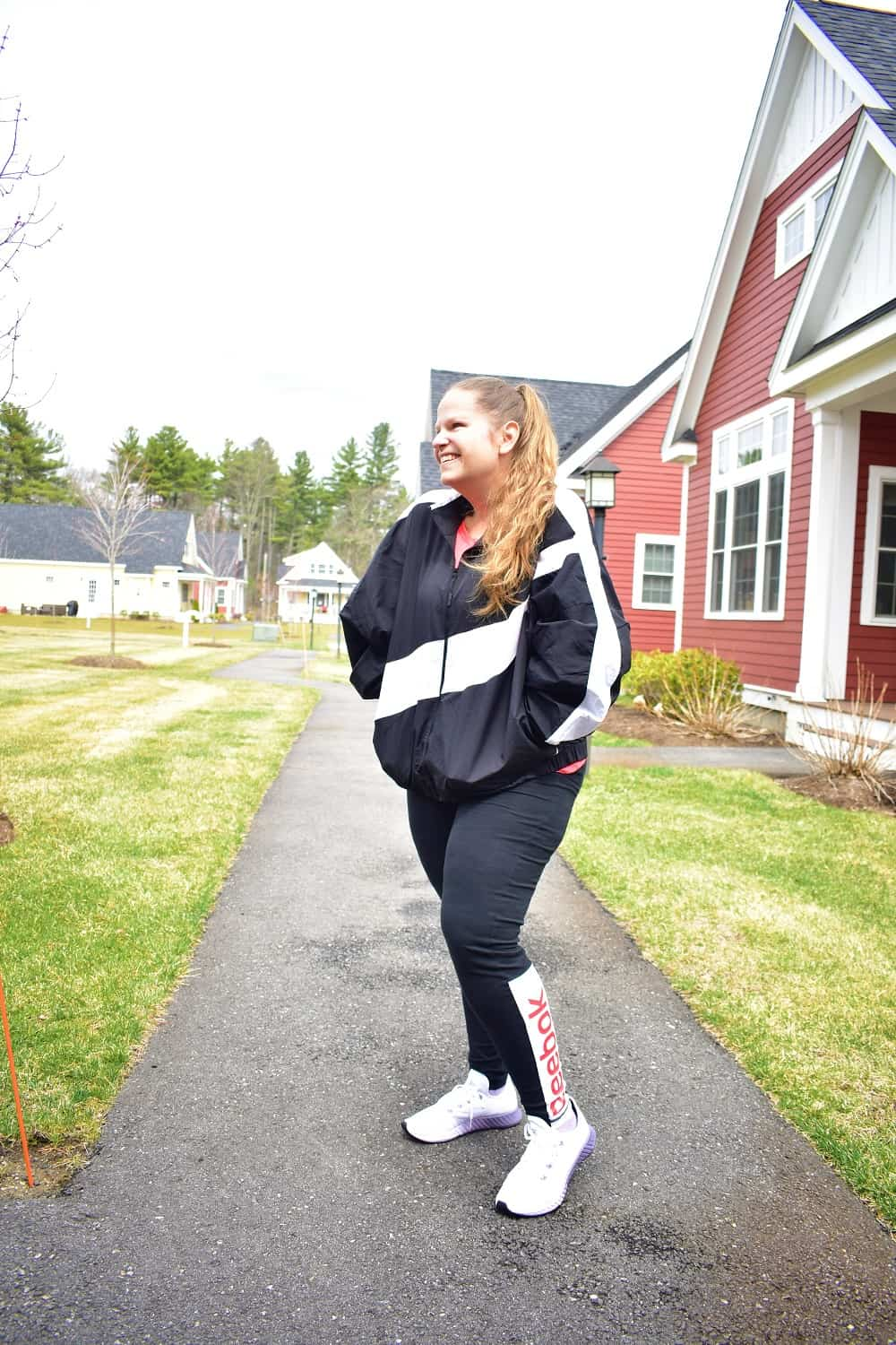 a woman getting ready to start a 30 day walking challenge outside in workout gear