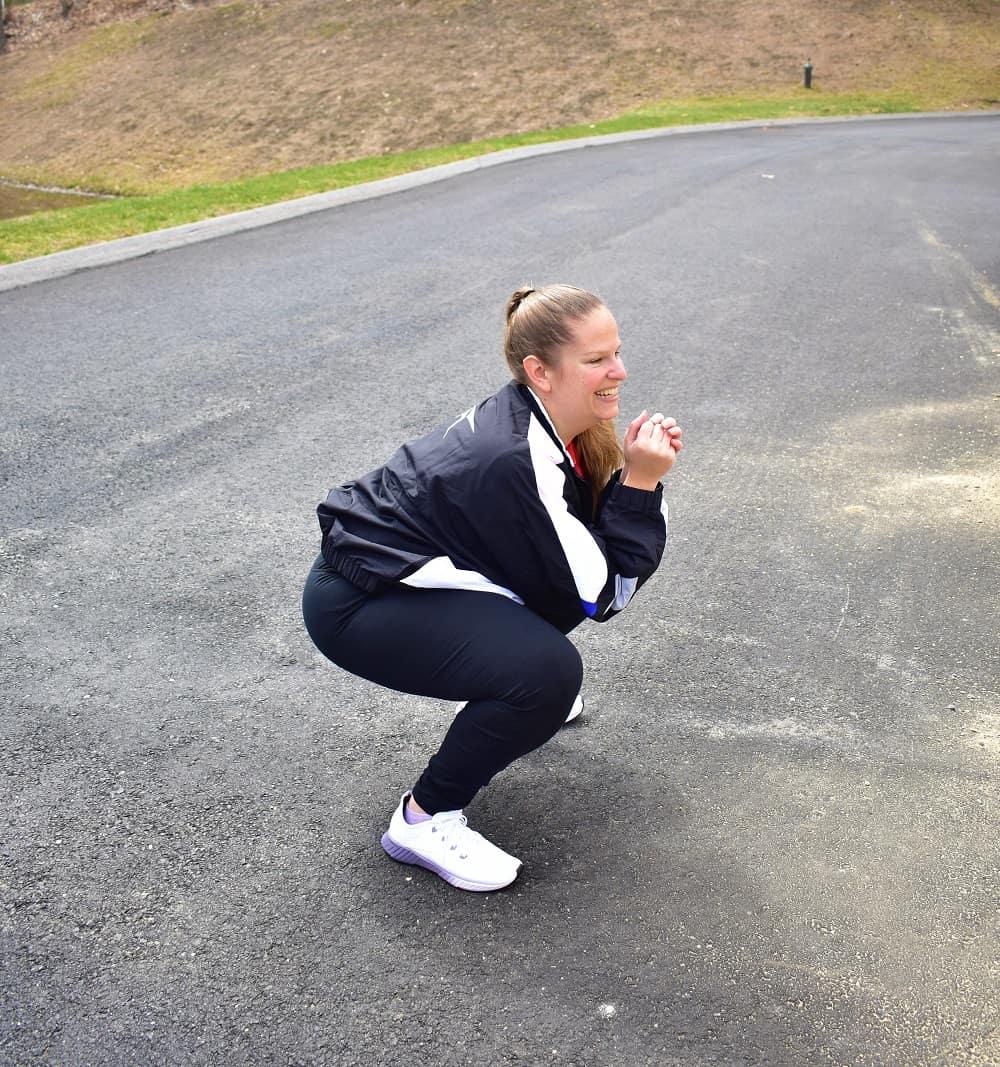 a woman doing squats outside