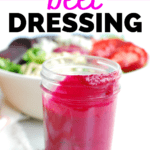 a small jar filled with beet dressing, next to a bowl of salad
