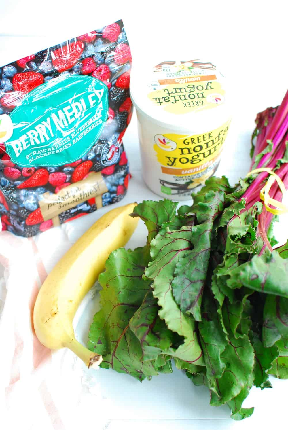 a bag of frozen berries, a container of greek yogurt, a banana, and a bunch of beet greens
