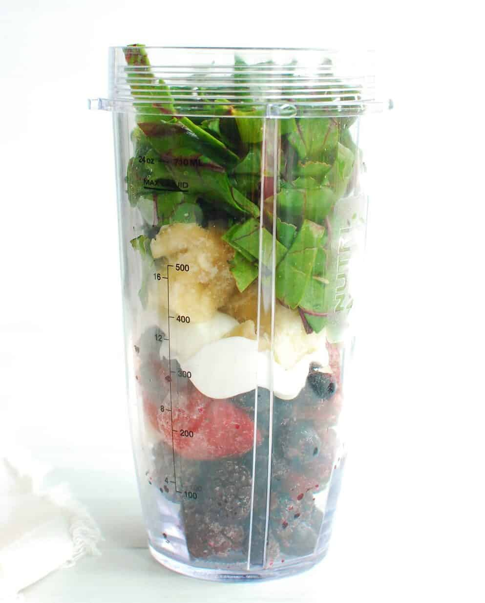 A blender cup full of ingredients to make a smoothie