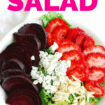 a strawberry beet salad in a large white bowl next to a cloth napkin