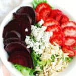 a white bowl filled with a strawberry beet salad next to a pink and white napkin