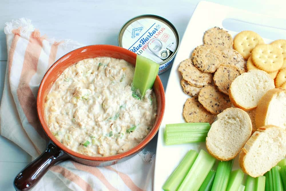 Hot version of canned salmon dip in a ramekin, next to crackers, celery, and baguettes