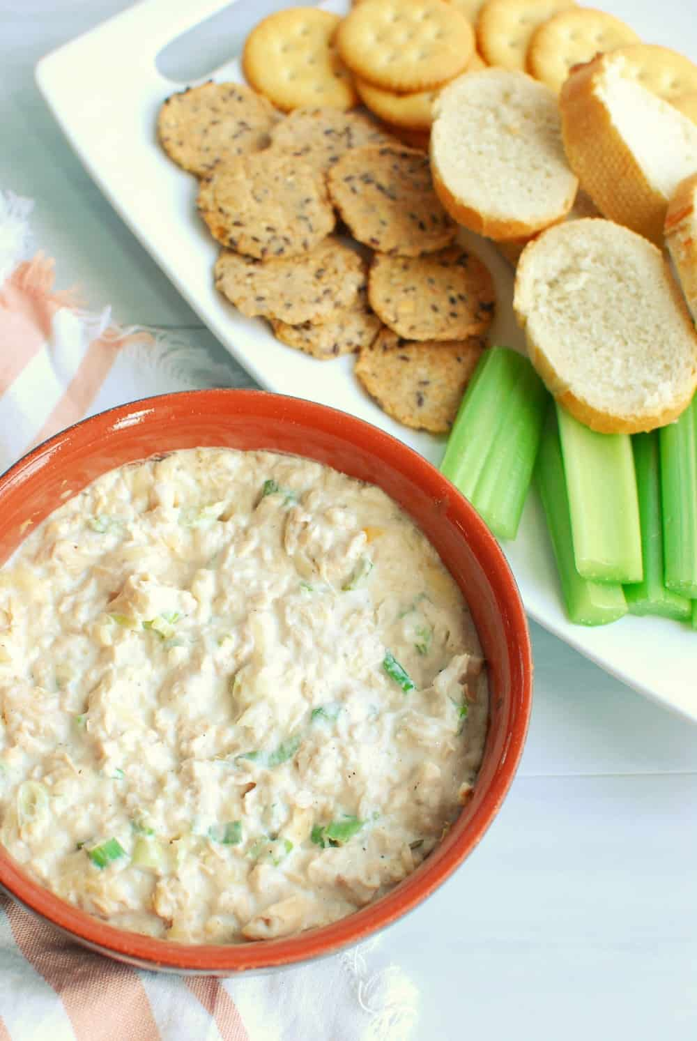 a ramekin full of hot salmon dip, next to dippers like celery and baguettes