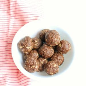 a bowl of coffee protein balls next to a pink napkin