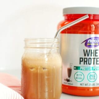 a mason jar with protein coffee next to a container of protein powder