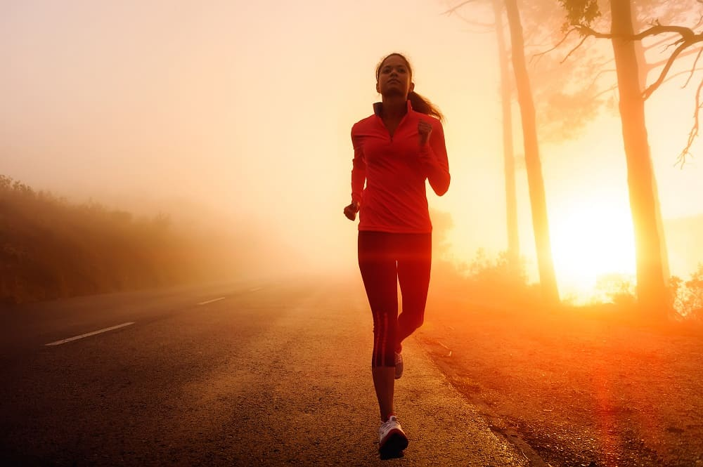 a woman running outside during sunrise
