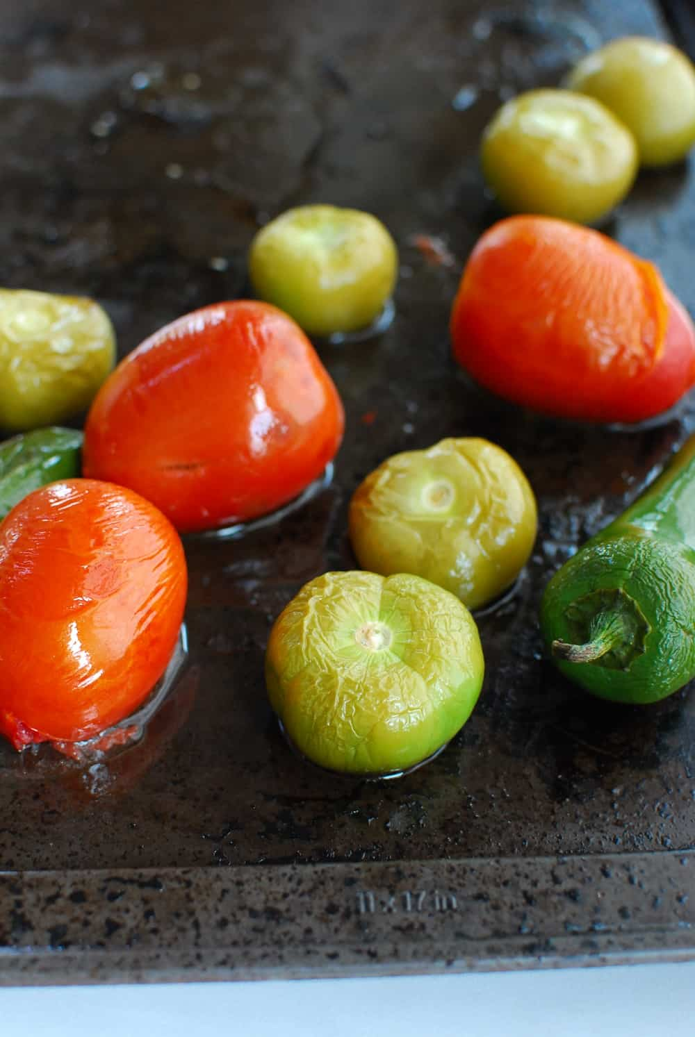 roasted tomatillos, tomatoes, and jalapenos on a baking sheet