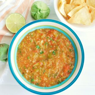 a bowl full of tomatillo and tomato salsa, next to a lime, some tomatillos, and some tortilla chips