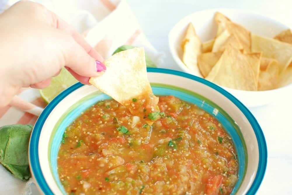 a woman dipping a tortilla chip into a bowl of tomatillo and tomato salsa