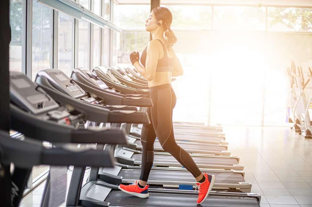 a woman running on a treadmill inside a gym