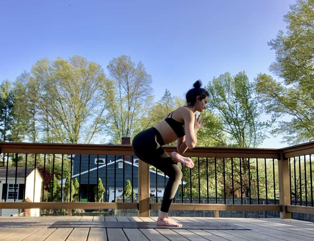a woman doing a standing figure four yoga post outdoors on a deck