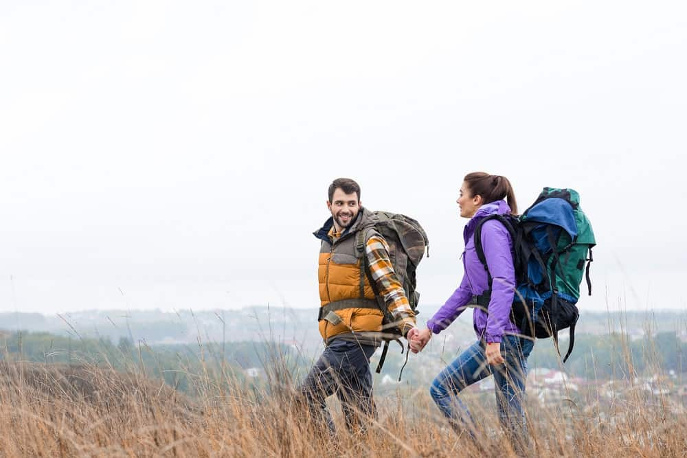 a couple taking a hike together outdoors with hiking backpacks