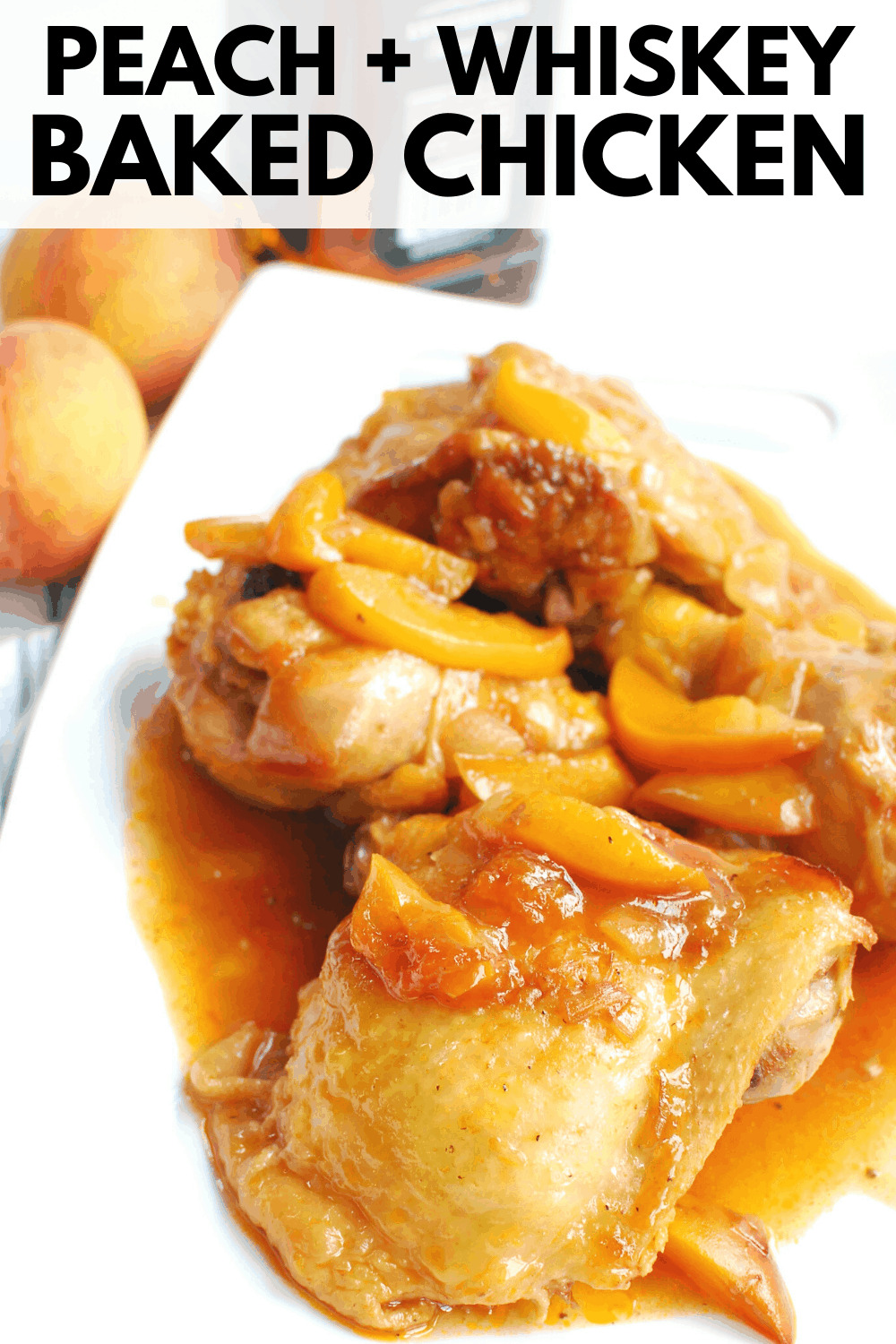 peach whiskey chicken on a white platter next to two peaches and a bottle of whiskey