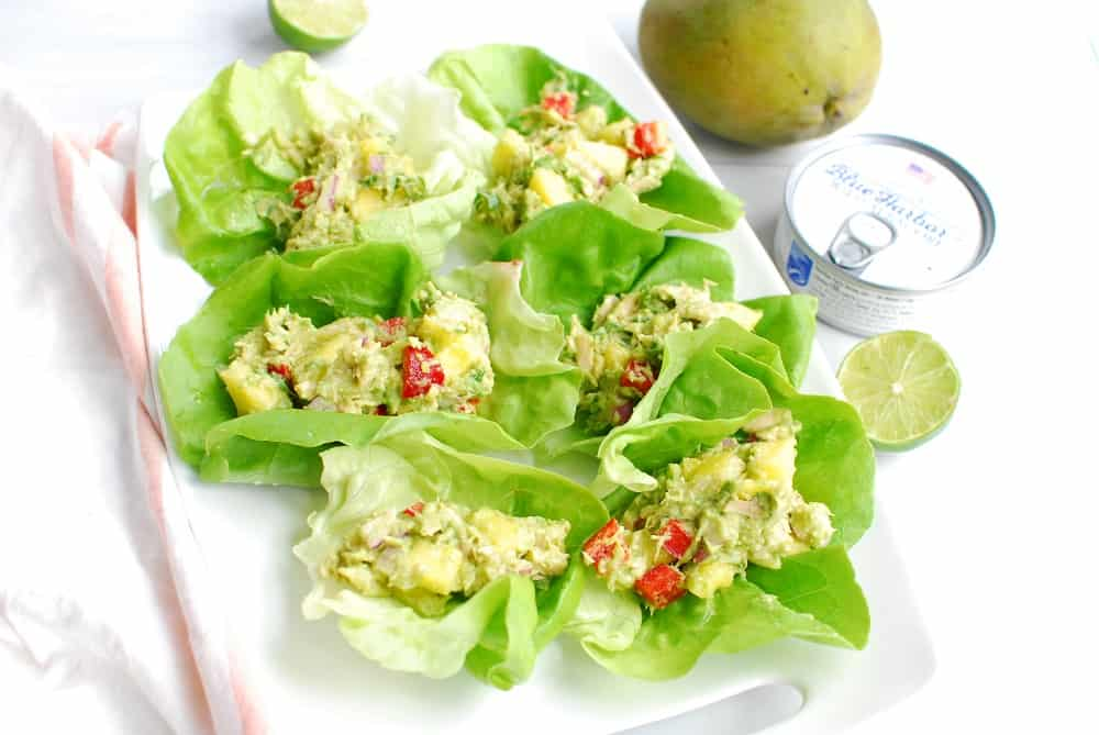 a white platter with six tuna lettuce wraps next to a can of tuna and a mango