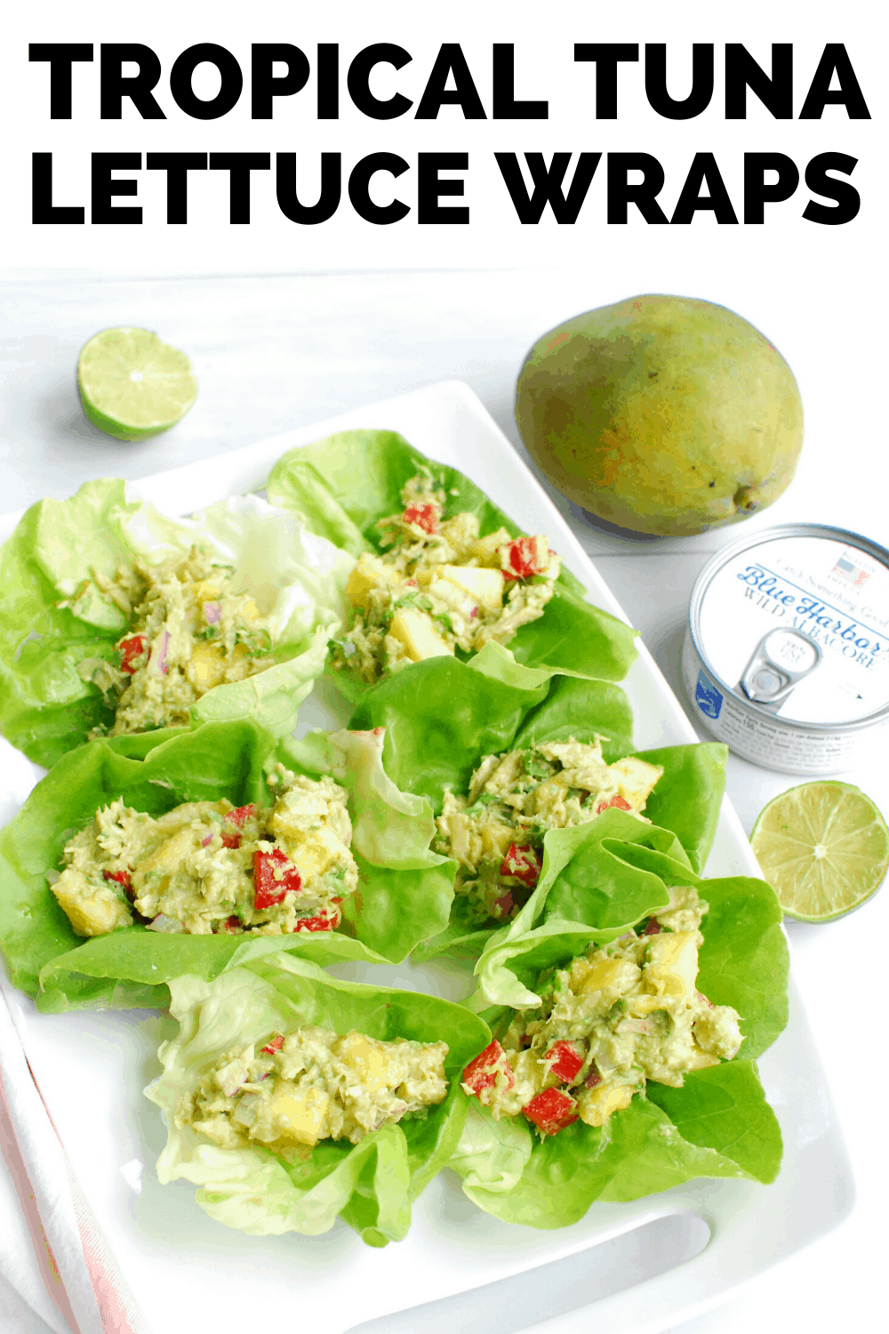 several tropical tuna lettuce wraps on a white serving platter next to a can of tuna and a mango