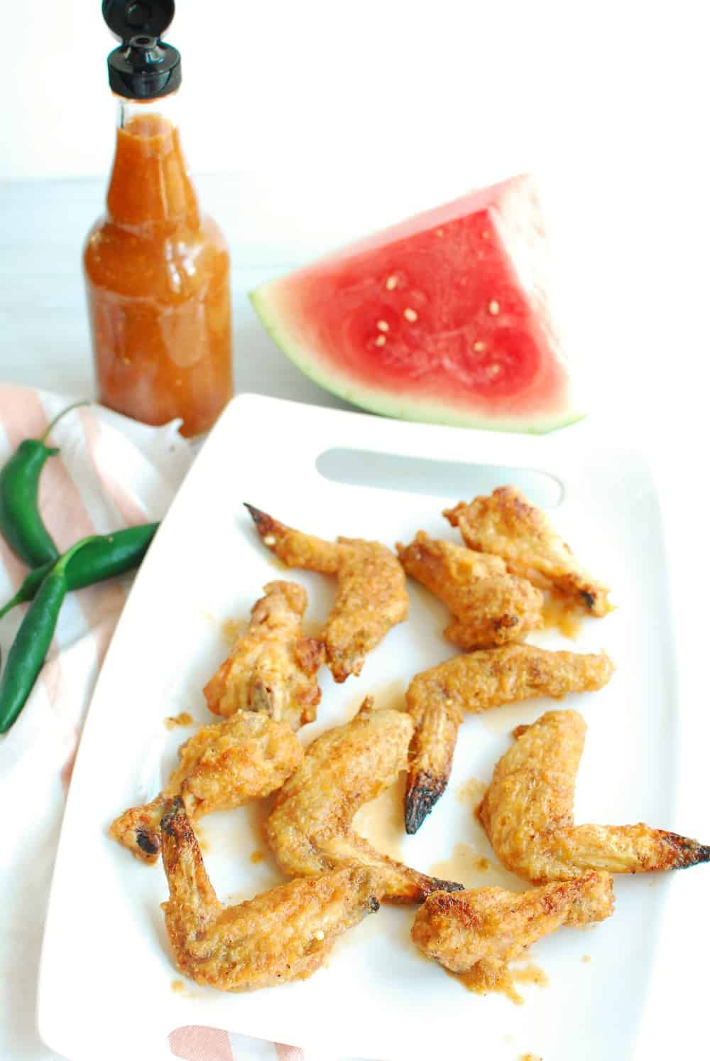 a platter full of baked chicken wings tossed in watermelon hot sauce