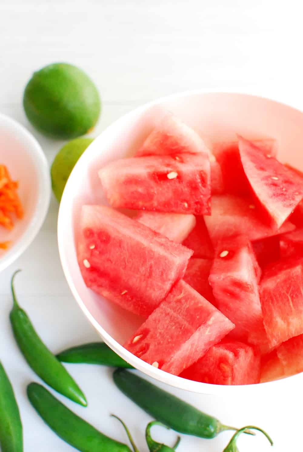 a bowl full of chopped watermelon next to some serrano peppers and a lime