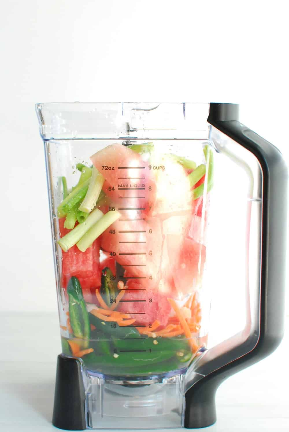 a blender full of watermelon, peppers, scallions, and other ingredients to make hot sauce