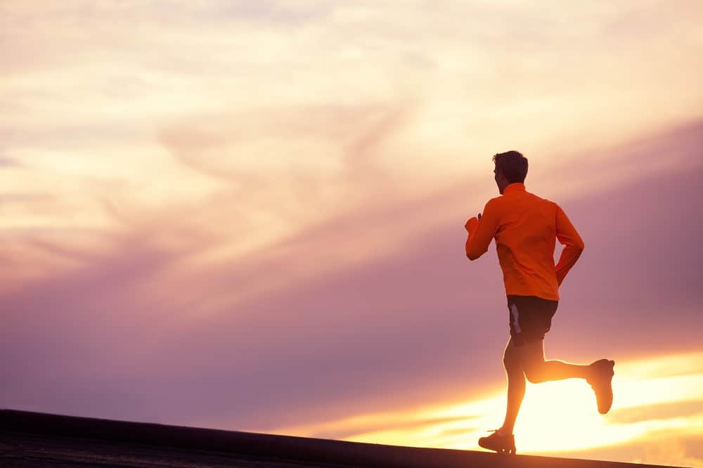 a man doing a long distance run at sunset outside