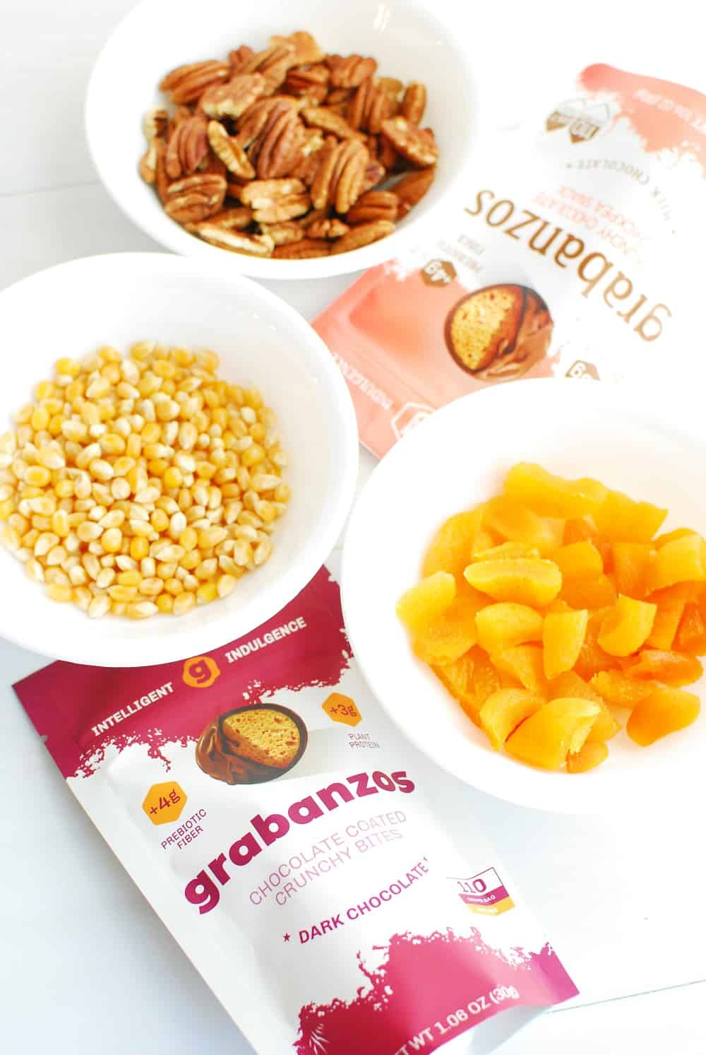 a bag of grabanzos, a bowl of popcorn kernels, a bowl of dried apricots, and a bowl of pecans