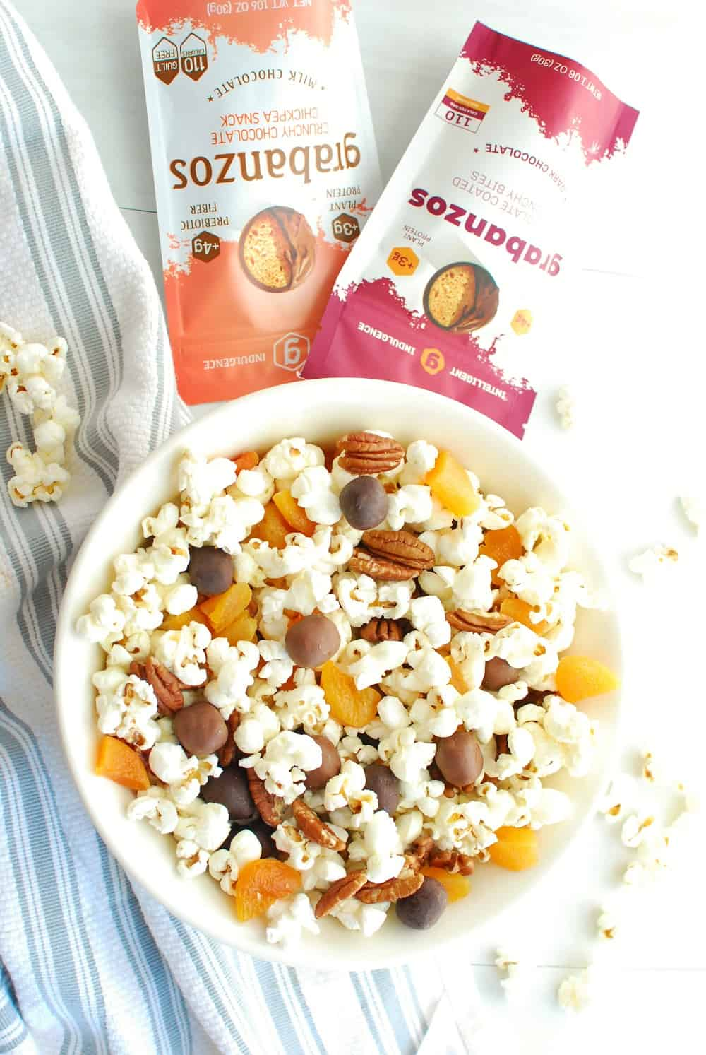 a big bowl of popcorn snack mix next to a napkin, some extra popcorn, and chocolate covered chickpeas
