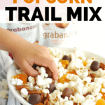 a kids hand reaching into a bowl of popcorn trail mix to grab some