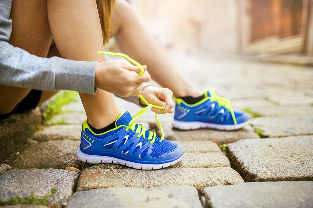 a woman lacing up her sneakers getting ready to go for a run