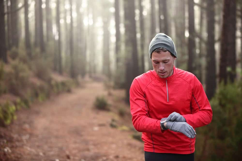 trail runner looking at his heart rate monitor watch