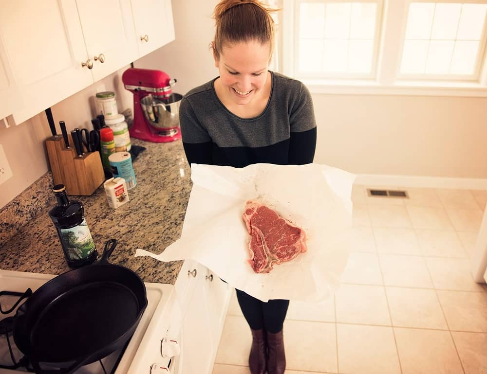 a woman holding a steak in butcher paper