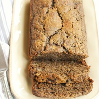 a loaf of buckwheat banana bread on a plate with two slices cut