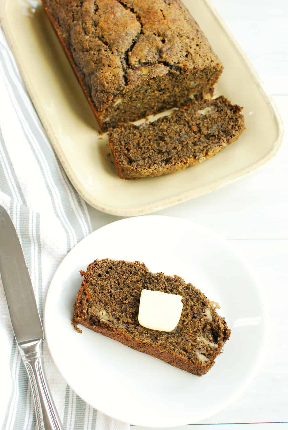 a slice of buckwheat banana bread with a pat of butter on a plate next to the rest of the loaf