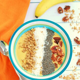 a pumpkin smoothie bowl with toppings of granola, chia seeds, coconut, and pecans