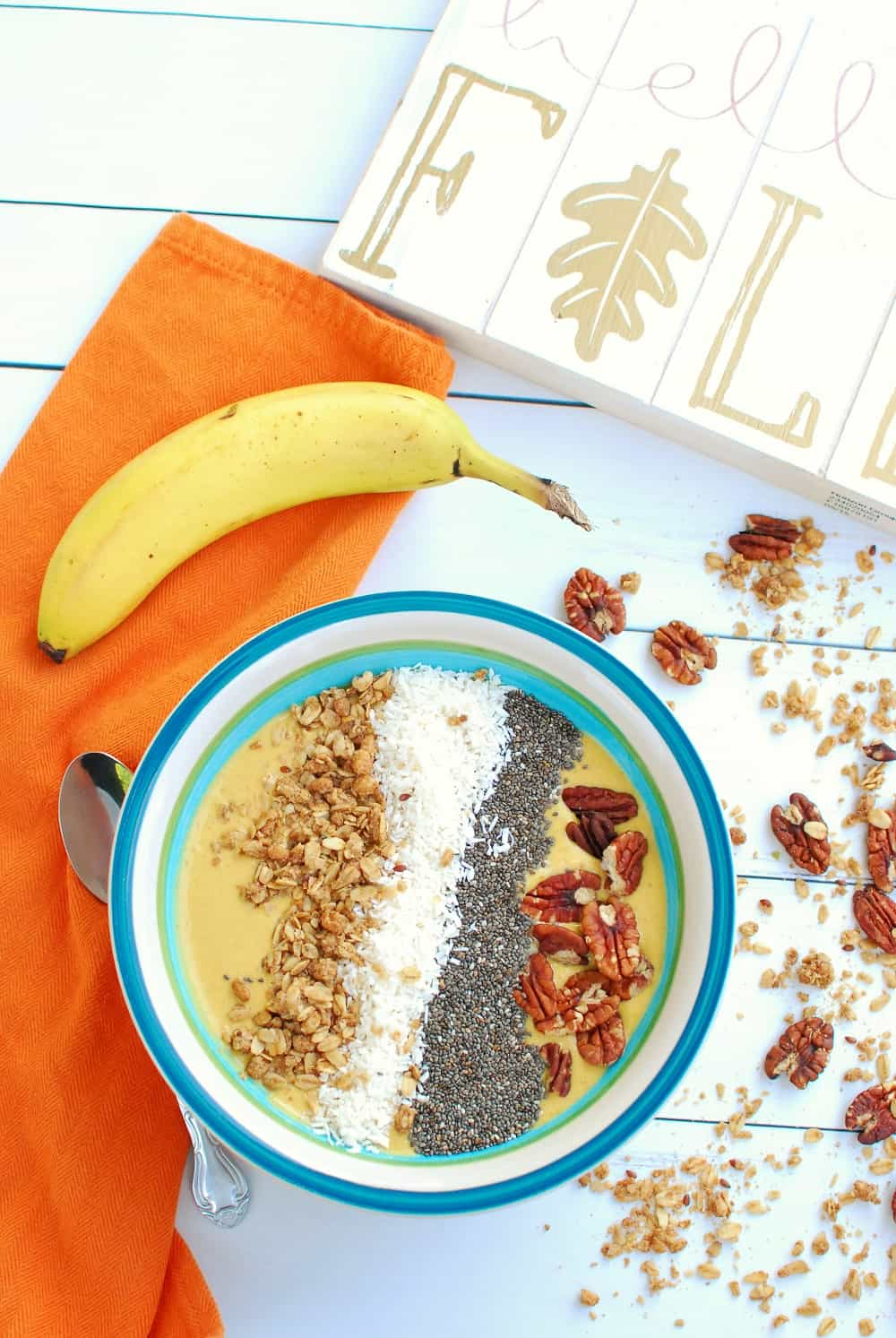 a pumpkin smoothie bowl next to an orange napkin, a banana, and some scattered granola and pecans
