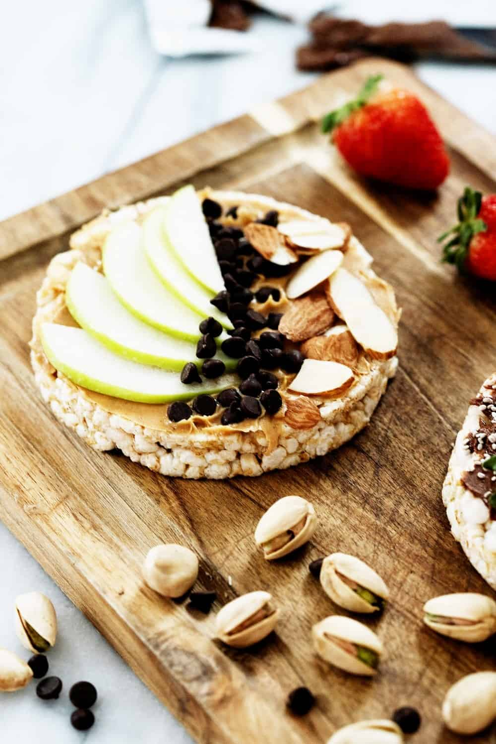 a rice cake topped with nut butter, apples, slivered almonds, and mini dark chocolate chips