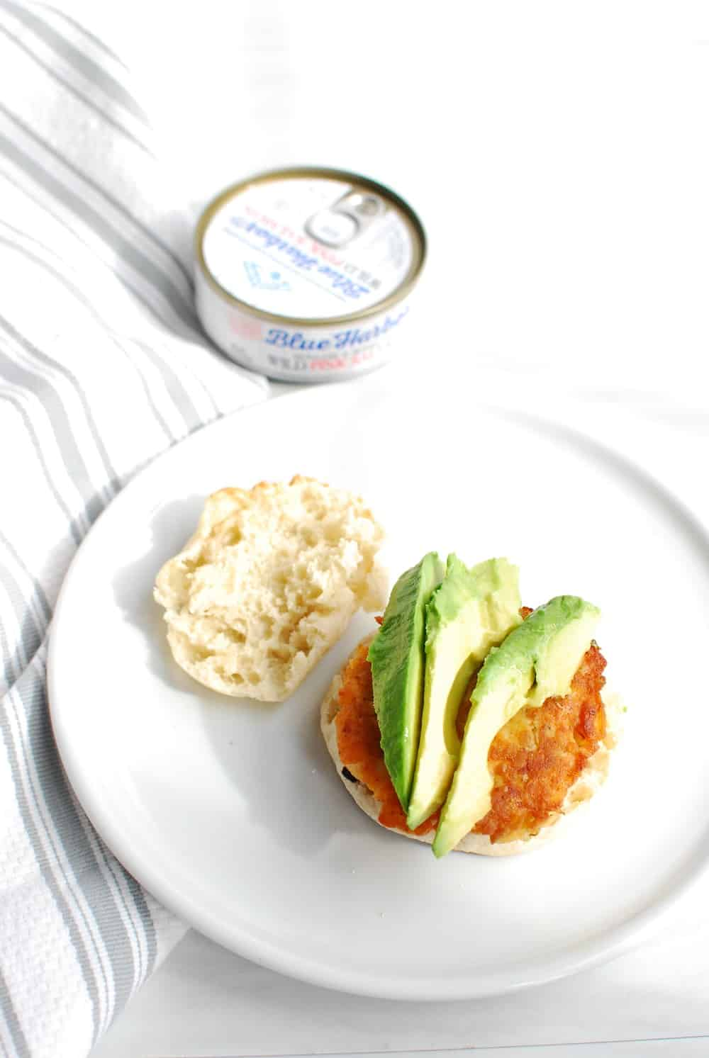 an english muffin topped with a salmon patty and several slices of avocado, next to a can of salmon