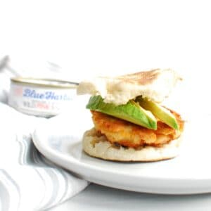 a salmon breakfast sandwich with avocado on a white plate