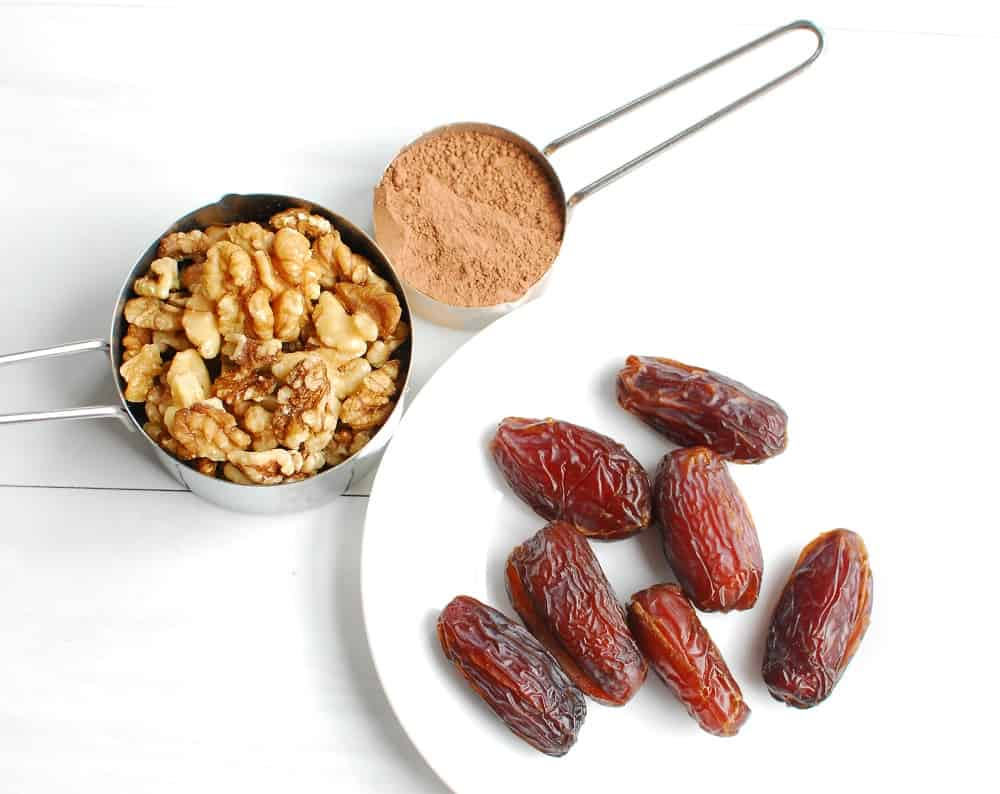 dates on a plate, walnuts in a measuring cup, and cocoa powder in a measuring cup