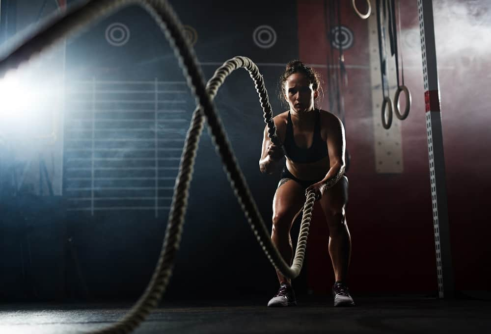 A woman exercising with ropes in the gym.