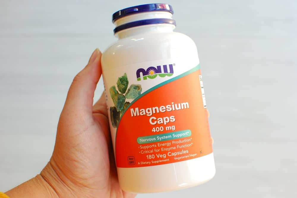 a magnesium supplement bottle in a woman's hand