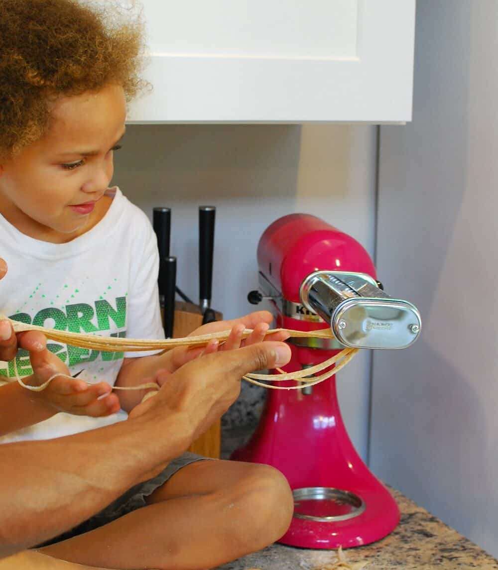 a little boy making fettuccine noodles with a stand mixer attachment