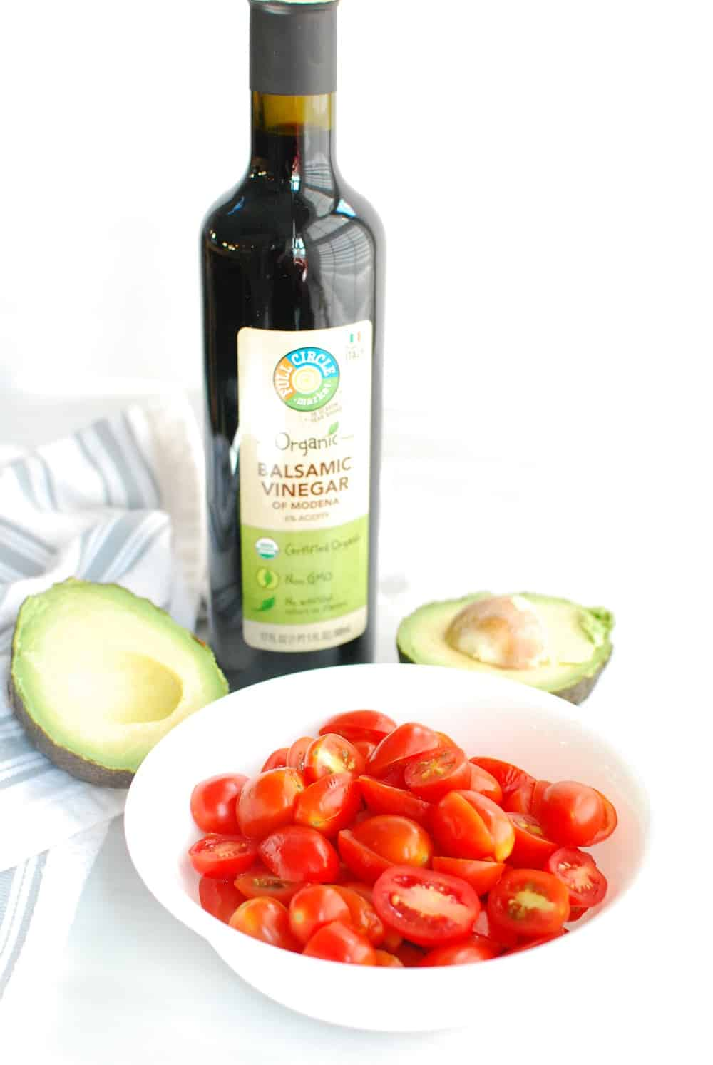 a bottle of balsamic vinegar next to a bowl of cherry tomatoes and a halved avocado