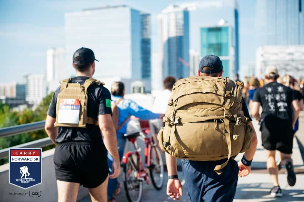 two men carrying weighted backpacks walking in a 5K race