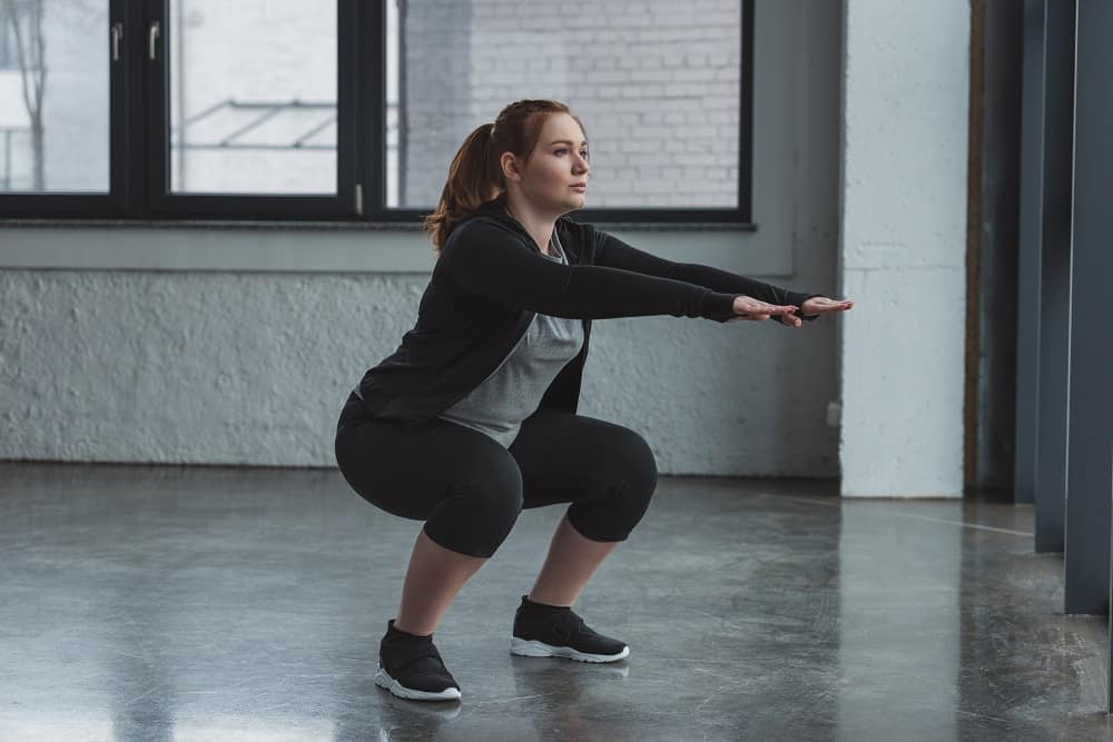 a woman doing a squat
